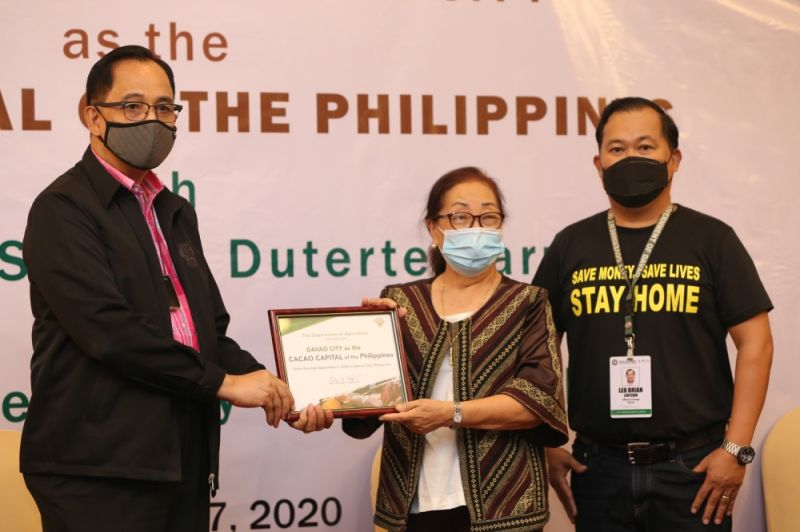 CACAO CAPITAL. (From left) Agriculture Secretary William Dar presents the certificate of recognition to Charito Puentespina of Malagos Chocolate and City Agriculture's Office head Leo Leuterio. (Photo from William Dar's Facebook page)