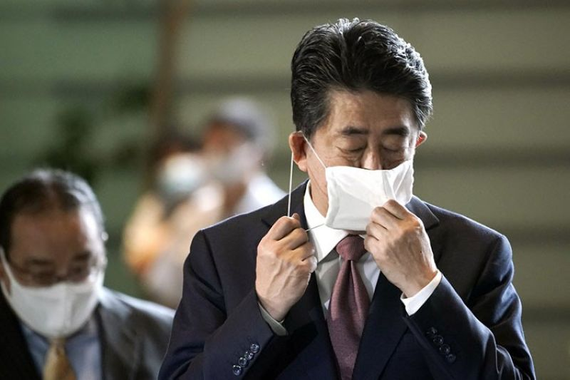 Japan's outgoing Prime Minister Shinzo Abe takes off his face mask as he arrives at the prime minister's office for a cabinet meeting Wednesday, Sept. 16, 2020, in Tokyo. Abe and his Cabinet resigned, clearing the way for his successor Yoshihide Suga to take over after parliamentary confirmation later in the day. (AP Photo)