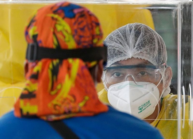 MANILA. A health worker ask questions of visitors as they conduct mass testing for Covid-19 in Manila, Philippines on Friday, May 8, 2020. (AP)