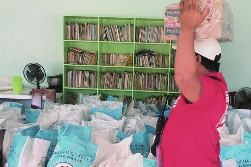 RELIEF GOODS. An official of Brgy. Bato in Toledo City helps unpack relief goods that were purchased using ER 1-94 funds remitted by AboitizPower subsidiary Therma Visayas Inc. (Contributed)