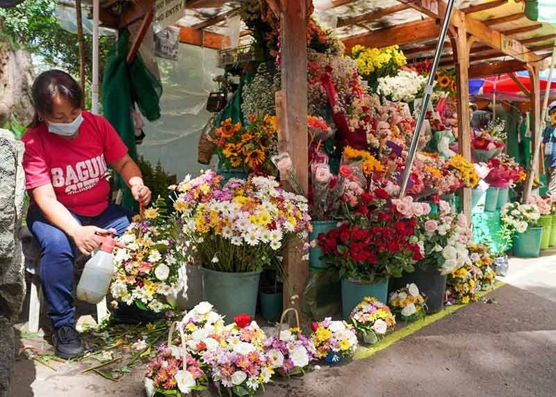 STRUGGLING. Bernadeth Bagana, one of the 24 flower vendors in Burnham Park, struggle to keep their business afloat due to low sales. As All Souls' Day nears, flower vendors hope to recover from months of closure due to the different community quarantine. (Jean Nicole Cortes)