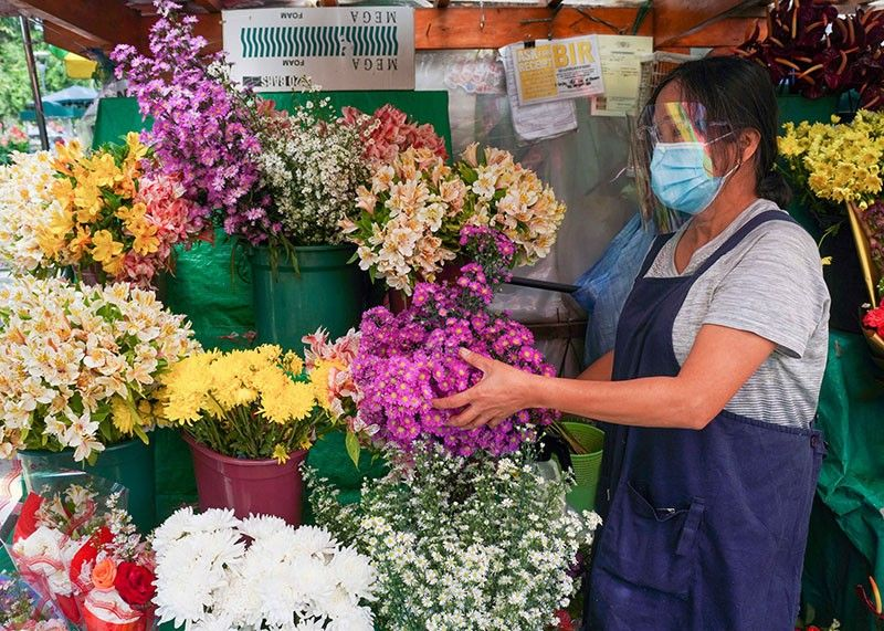 HOPING. A flower vendor at Ganza in Burnham Park waits for customers, hoping to sell more this coming All Souls Day. Photo by Jean Nicole Cortes