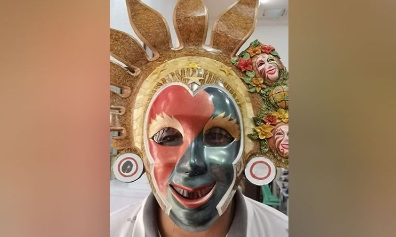 BACOLOD. Negros Occidental Provincial Tourism Office staff Raymond Alunan wears a MassKara-designed mask to welcome overseas contract workers, locally stranded individuals, and other important travelers who come in and go out of Bacolod City via the Bacolod-Silay airport. (Contributed photo)