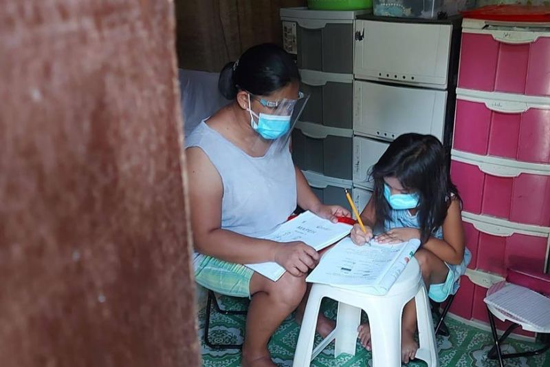 NEW SETUP. Instead of tending to her small business in Sitio Langub, Brgy. Guadalupe, Cebu City, a mom spends her time guiding her child in answering modules as part of the new learning system this school year. (AMPER CAMPANA)