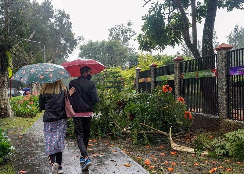 Promenaders in Burnham Park avoid a fallen branch of a tree caused by the continuous rains brought about by Tropical Storm Pepito. Photo by Jean Nicole Cortes