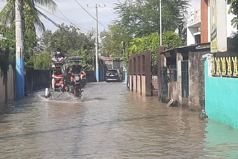 JACKED-UP. A tricycle lifted by few feet was able to cross flooded roads in Macabebe town, which was submerged by rainwaters. Photo by (Princess Clea Arcellaz)