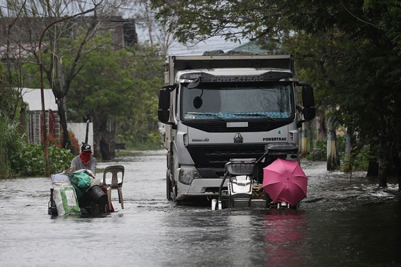 PAMPANGA. Motorists with an umbrella negotiate a flooded road due to Typhoon Quinta (Molave) in Pampanga province on Monday, October 26, 2020. (AP)