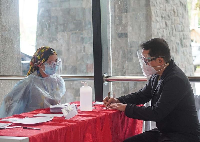 PROTOCOL. A man undergoes triage upon entry at the Baguio Convention Center. All establishments require the public to wear face masks, face shields and fill out health declaration forms in order to curb the spread of Covid-19. (Jean Nicole Cortes)