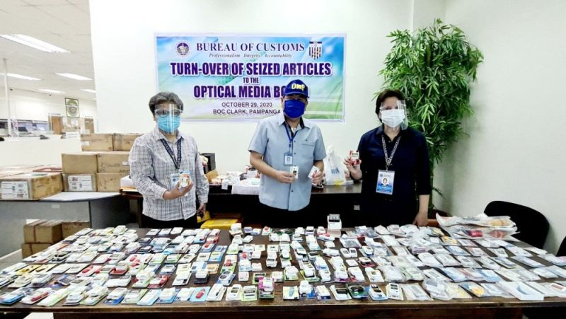 SEIZED ELECTRONIC DEVICES. Bureau of Customs Port of Clark District Collector Atty. Ruby Alameda (R) and Deputy District Collector for Operations Wilnora Cawile (L) turned over on October 29, 2020 to Edgardo Lara, internal auditor of the Optical Media Board, 2,500 pieces of assorted bank card and electronic magnetic storage devices that were seized by Customs police inside Clark. (Chris Navarro)