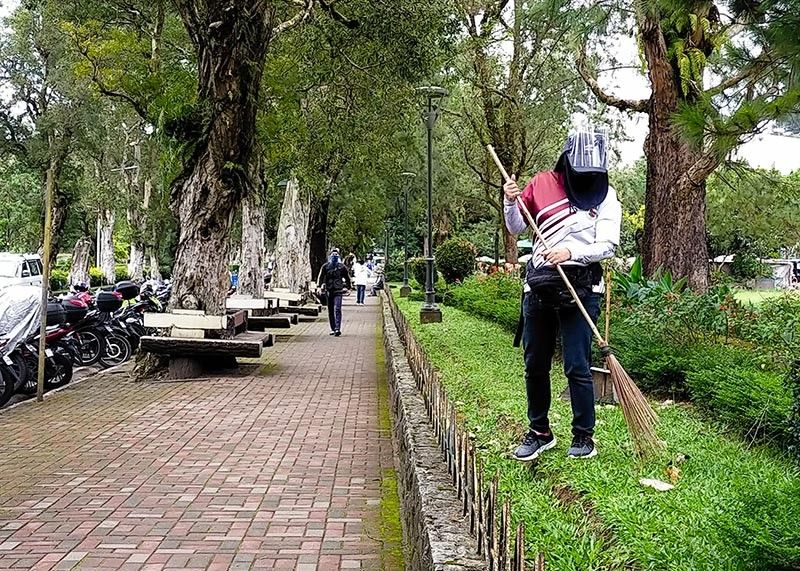 UNSUNG HERO. A utility worker maintains the cleanliness of Burnham Park amid the pandemic. More tourists are expected to visit the Summer Capital with the easing of travel restrictions in Baguio City. (Jean Nicole Cortes)