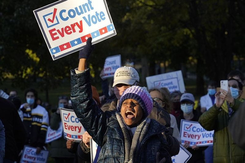 Demonstrator Karen Louise Gonsalves, of Boston, center, displays a placard, Wednesday, Nov. 4, 2020, during a protest on the Boston Common, in Boston, as ballots continue to be counted in some battleground states for the general election. (AP Photo)