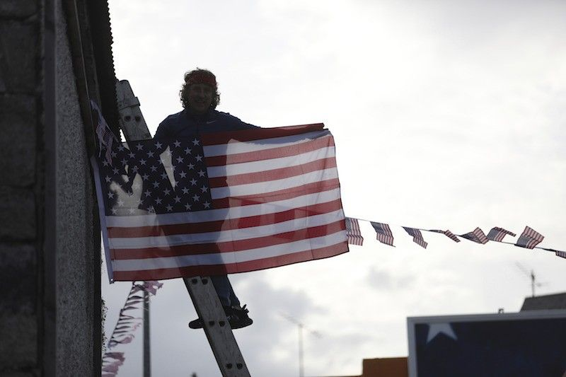 A man hangs a US flag up in the town of Ballina, North West of Ireland, Saturday, Nov. 7, 2020. Ballina is the ancestral home of US President elect Joe Biden. Biden was elected Saturday as the 46th president of the United States, defeating President Donald Trump in an election that played out against the backdrop of a pandemic, its economic fallout and a national reckoning on racism. (AP)