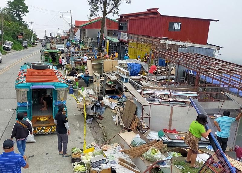 DEMOLITION. Vendors along Marcos Highway in Sto. Tomas, Baguio City pick up their belongings as the City Buildings and Architecture Office implement  demolition order to stalls obstructing the road-right-of-way along the  national road. Some 11 stall owners in the area lost their livelihood due to the demolition. (Jean Nicole Cortes)