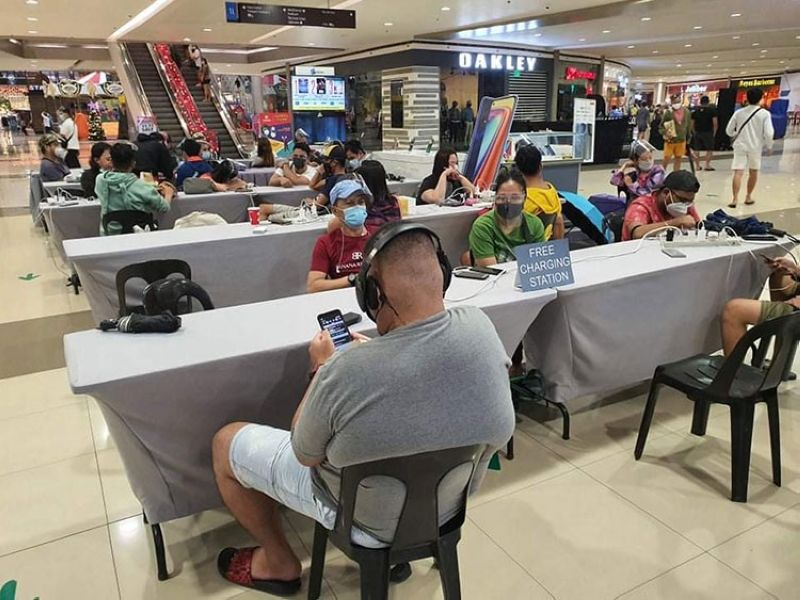 FREE CHARGING. Individuals affected by blackouts in Angeles City, Mabalacat City, and other nearby areas charge their phones at SM City Clark during the onslaught of Typhoon Ulysses. (Contributed photo)