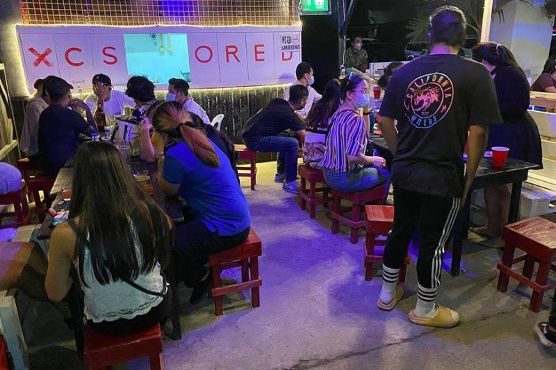 KUSTOMER SA RESTO-BAR: Mao kini ang mga kustomer sa usa ka resto-bar sa uptown sa dakbayan sa Sugbo nga walay social distancing ug ubang kalapasan sa health protocol busa gipapauli sa kapulisan. (Benjie B. Talisic)