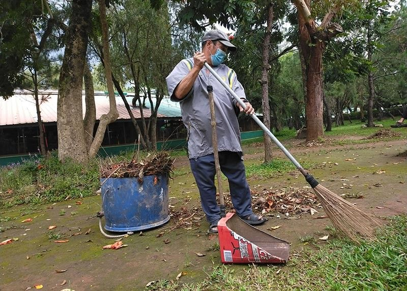 MAINTENANCE. Even without tourists, a utility worker maintains cleanliness at Burnham Park. (Jean Nicole Cortes)