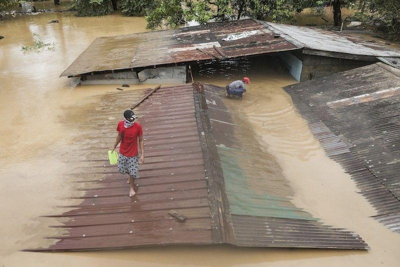 MANILA. A man walks on top of a roof of a submerged house as floods inundate villages due to Typhoon Vamco in Rizal province, Philippines on Thursday. November 12, 2020. (AP File)