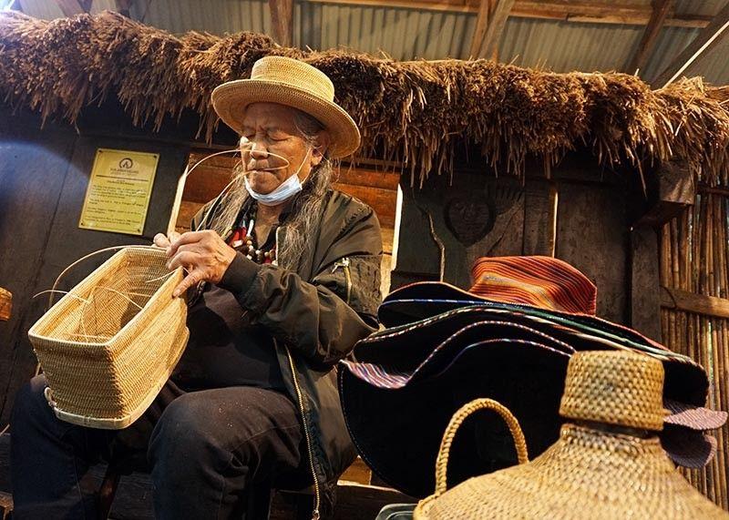 CRAFTSMAN. James Mangosan carefully crafts a rattan backpack known as