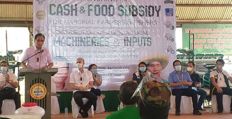 BACOLOD. Agriculture Secretary William Dar (standing) speaks at the launching and distribution of over P450 million worth of programs and projects for farmers, fisherfolk and local government units in Negros Occidental at the Pana-ad Park in Bacolod City Tuesday, December 8, 2020. (Erwin P. Nicavera)