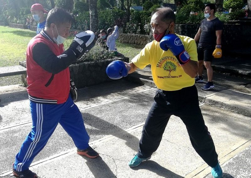 BAGUIO. Former boxing national coach Glicerio Catolico (left) works the mitts with fitness guru and Gintong Alay boxer Danilo Quinto (right) at Burnham Park, as both defy their age to stay fit amid the threat of Covid-19. (Photo by Milo Brioso)