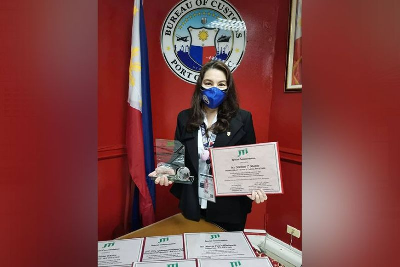 COMMENDATION. Port of Subic Collector Maritess Martin holds the certificate and plaque of commendation given by a Japanese cigarette company for the successful campaign against fake cigarette smugglers in Subic. (Contributed photo)