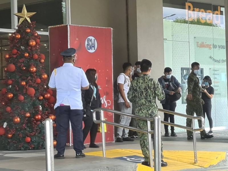 SAFETY AND HEALTH. Policemen and security guards check mall-goers entering SM City Pampanga to assure they are wearing face masks, face shields and observing social distancing as part of the Inter-Agency Task Force safety and health protocols. (Photo by Chris Navarro)