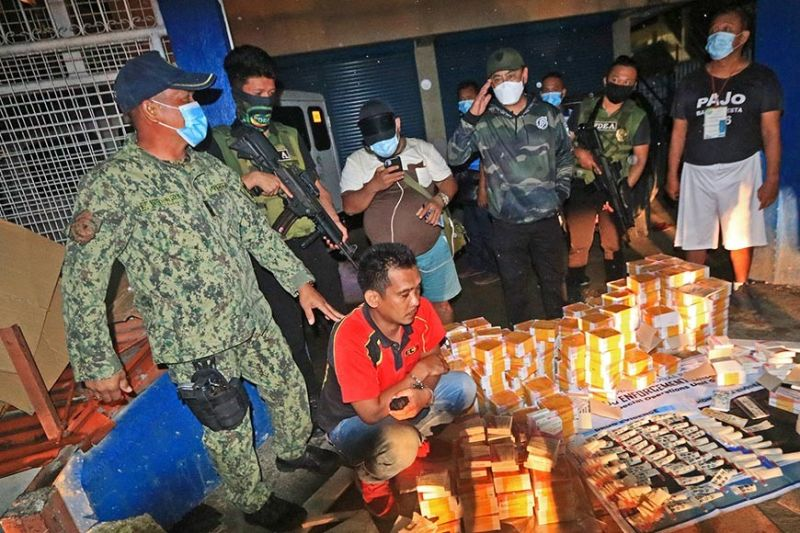 PARTY DRUGS. Lapu-Lapu City Mayor Junard Chan (standing fourth from left) gives a salute to the policemen and members of the Philippine Drug Enforcement Agency who caught Dioscoro Colo, 33, (crouching) with more than P5 million worth of Nubain, Tuesday, Jan. 12, 2021, believed to be for illegal distribution to Sinulog party goers. Capt. Alcon Escosura (leftmost), acting chief of Lapu-Lapu City's Police Station 3, presents the suspect and the contraband seized. (ALAN TANGCAWAN)