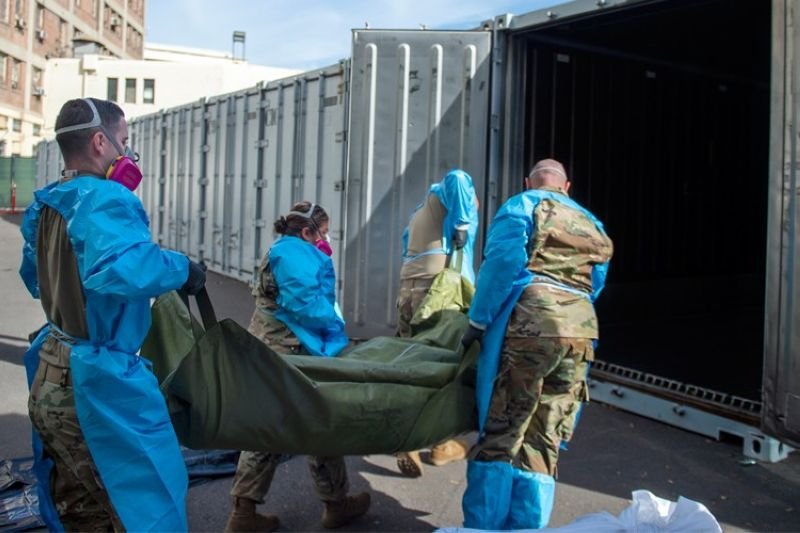 In this Jan. 12, 2021 photo provided by the Los Angeles County Department of Medical Examiner-Coroner, National Guard members assisting with processing COVID-19 deaths, placing them into temporary storage at the medical examiner-coroner's office in Los Angeles. The seven-day rolling average of daily deaths is rising in 30 states and the District of Columbia, and on Monday, Jan 18, 2021, the U.S. was approaching 398,000, according to data collected by Johns Hopkins University, by far the highest of any country in the world. (Los Angeles County Department of Medical Examiner-Coroner via AP, File)