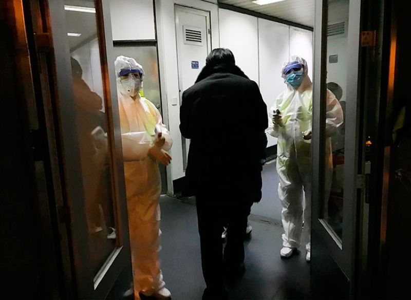 CHINA. In this January 22, 2020 file photo, health officials in hazmat suits wait at the gate to check body temperatures of passengers arriving from the city of Wuhan, at the airport in Beijing, China. (AP)