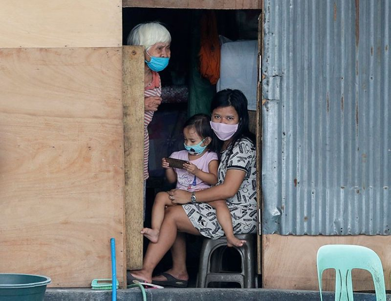 MANILA. Residents wearing protective masks looks from inside their shanty as the military provides cooked food at a slum area during an enhanced community quarantine to prevent the spread of the new coronavirus in Manila, Philippines on April 20, 2020. (AP File)