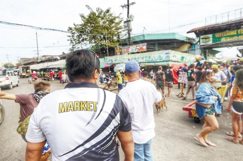 ARRESTING UNMASKED. Members of the Market Operations Division of the Cebu City Government bring people they had apprehended earlier at the Pardo Public Market to the division's office in Unit 3 of the Carbon Public Market Tuesday, Jan. 26, 2021, for the recording of their details before their transfer to the Barangay Tejero gym for the assessment of their penalty. In the morning, people from the Carbon Market were also apprehended for similarly not wearing or incorrectly wearing masks. Cebu City is battling a post-holiday surge in Covid-19 cases, with new cases returning to double-digit levels daily since Dec. 29, 2020. (AMPER CAMPAÑA)