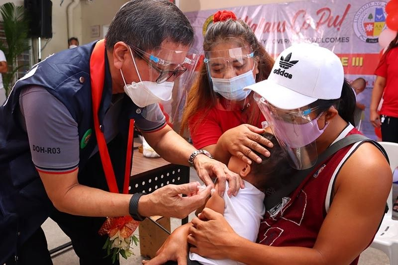 SUPPLEMENTAL IMMUNIZATION. Health Undersecretary Gerardo Bayugo administers measles, rubella, and polio vaccines to an Angeleño child during the regional launching of the Measles, Rubella, Oral Polio Vaccine Supplemental Immunization Activity Phase 2 held in Angeles City. (Angeles City Information Office)