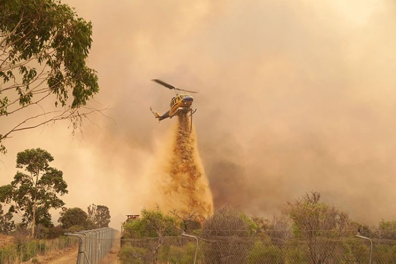 In this photo provided by Department of Fire and Emergency Services, a helicopter drops fire retardant on a fire near Wooroloo, northeast of Perth, Australia, Tuesday, Feb. 2, 2021. An out-of-control wildfire burning northeast of the Australian west coast city of Perth has destroyed dozens of homes and was threatening more. (AP photo)