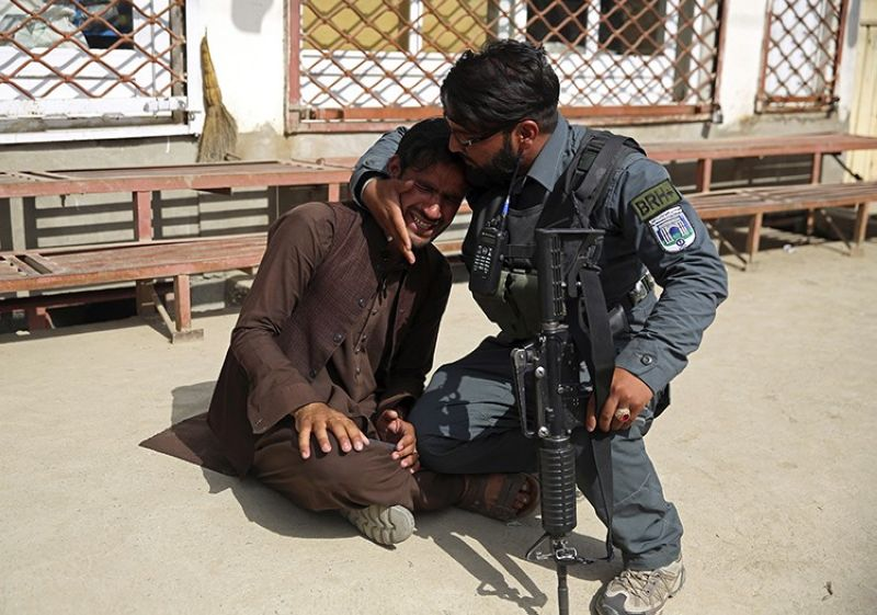 In this May 12, 2020 file photo, an Afghan policeman comforts a man after an attack on a maternity hospital that killed 24 people, in the Afghan capital Kabul. Afghanistan is supposed to be moving toward peace. But Kabul's residents fear the frequent bombings in the past months, large-scale attacks, kidnappings for ransom, armed men in broad daylight robbing stores, people in parks and cars stuck in traffic, are a sign it is instead entering yet another phase in decades of war.(AP Photo)