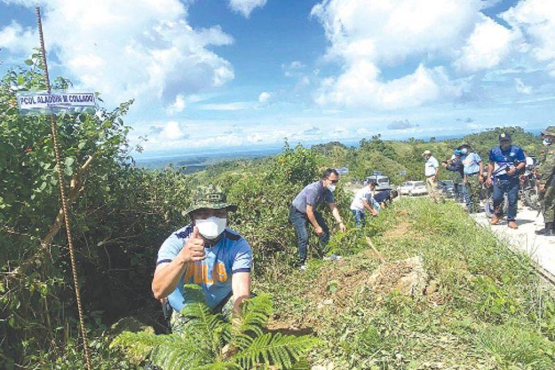TREE PLANTING SA TUBURAN : Ang kapulisan sa lalawigan sa Sugbo sa ilang tree planting activity sa bukirang dapit sa lungsod sa Tuburan. / Benjie B. Talisic