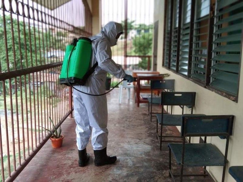 CEBU. In this photo taken in August 2020, an employee of the Mandaue City Disaster Risk Reduction and Management Office disinfects part of the Casili Elementary School. (File)