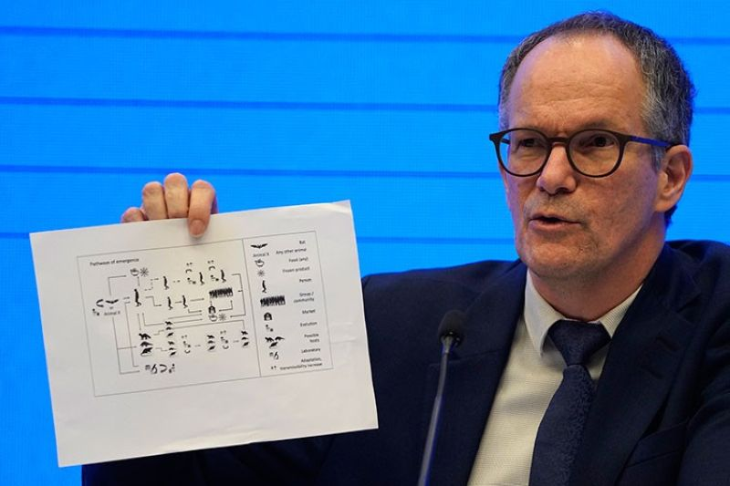 CHINA. Peter Ben Embarek of the World Health Organization team holds up a chart showing pathways of transmission of the virus during a joint press conference held at the end of the WHO mission in Wuhan in central China's Hubei province on Tuesday, February 9, 2021. (AP)