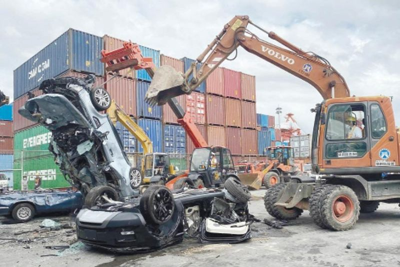 SMUGGLED. The Bureau of Customs Port of Cebu destroys five luxury cars worth P30 million on Feb. 9, 2021. The vehicles were seized because of questionable documents upon entry into the country. / BENJIE TALISIC