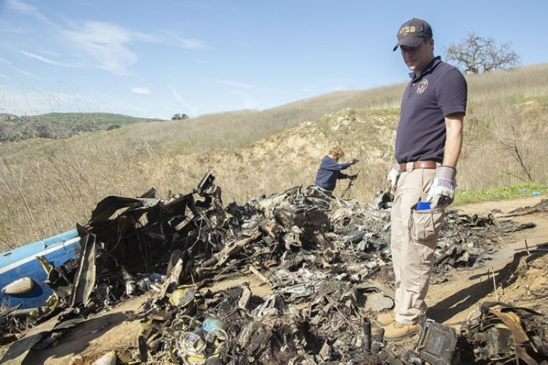 In this Jan. 27, 2020, file photo, provided by the National Transportation Safety Board, NTSB investigators Adam Huray, right, and Carol Hogan examine wreckage as part of the NTSB's investigation of a helicopter crash near Calabasas, Calif. Federal safety officials are expected to vote Tuesday, Feb. 9, 2021, on what likely caused the helicopter carrying Kobe Bryant, his 13-year-old daughter and seven others to crash into a Southern California hillside last year, killing all aboard. (James Anderson/National Transportation Safety Board via AP, File)