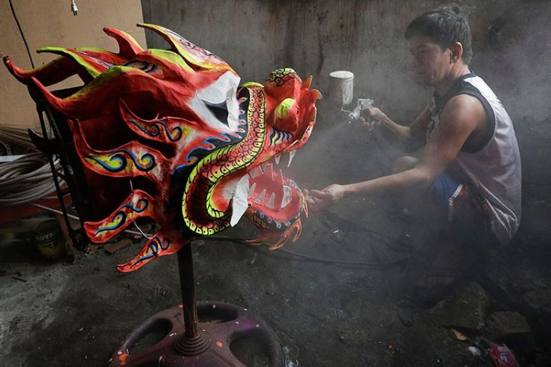 MANILA. Robert Sicat sprays a protective coating on a Dragon head at a creekside slum at Manila's Chinatown, Binondo Philippines on February 4, 2021. (AP)