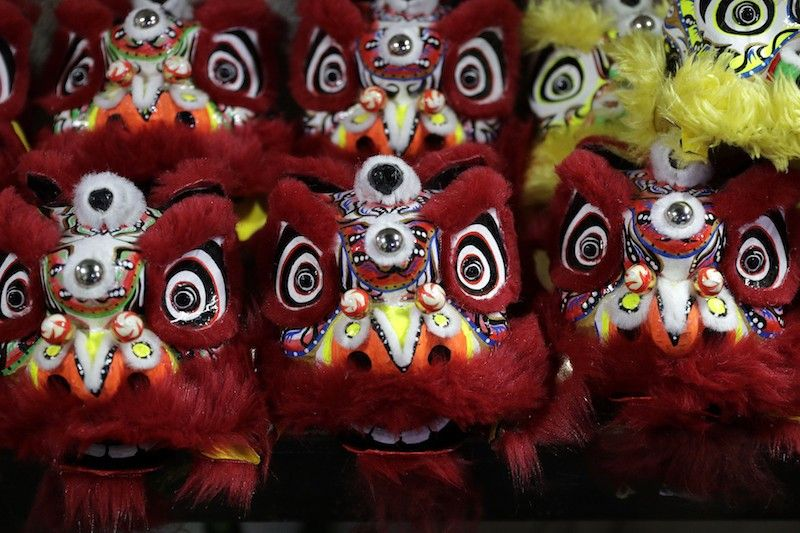 MANILA. Miniature lion heads are prepared for delivery as members of a dragon and lion dance group seek other ways to earn a living at a creekside slum in Manila's Chinatown, Binondo, on Feb. 8, 2021. Dragon and lion dancers won't be performing this year after the Manila city government banned the dragon dance, street parties, stage shows or any other similar activities during celebrations for Chinese New Year due to Covid-19 restrictions. (AP)