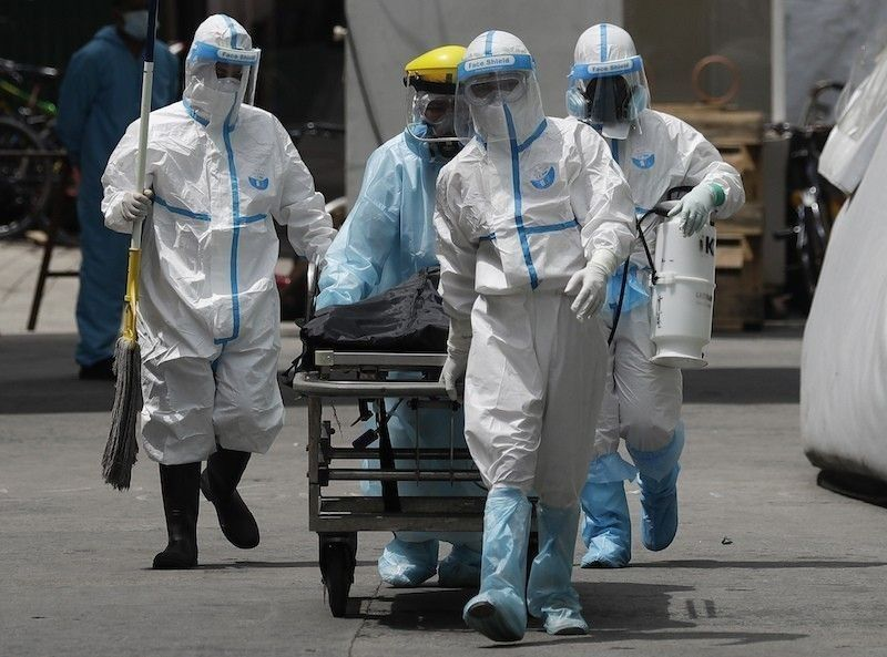 MANILA. Health workers wearing protective suits transport a corpse at a hospital in Manila on Aug. 6, 2020. (File)