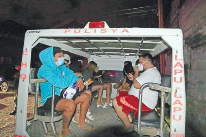 APPREHENDED. In Lapu-Lapu City, a group of youngsters are taken to the Gun-ob Police Station after they were caught drinking in Barangay Pajo after the 11 p.m. curfew on Friday, Feb. 19, 2021. / ALAN TANGCAWAN