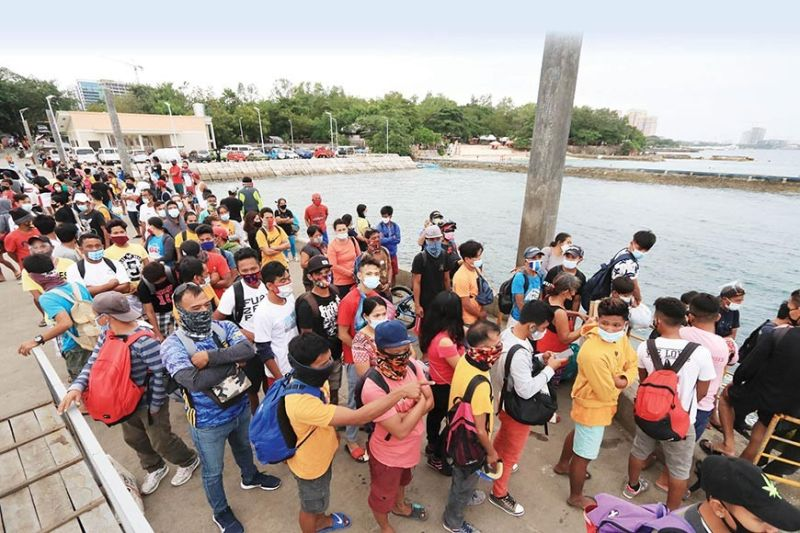 CANCELED TRIPS. Passengers to Olango are stranded in Angasil Port in Barangay Mactan, Lapu-Lapu City after the Philippine Coast Guard (PCG) suspended boat trips to the island on Saturday, Feb. 20, 2021. The approaching tropical storm Auring, which is expected to make landfall in Cebu Sunday night, Feb. 21, has generated big waves, making the crossing dangerous. According to the PCG, around 304 passengers were stranded in Cebu ports as trips were canceled when Central Visayas was placed under Tropical Cyclone Wind Signal No. 1. (ALAN TANGCAWAN)