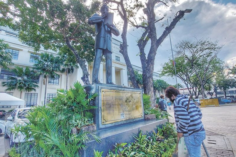 CHARTER DAY PREP. A Cebu City Hall worker cleans the monument of Don Vicente Rama, the author of the Cebu City Charter, on Tuesday, Feb. 23, 2021, in preparation for the wreath-laying ceremony for the city's 84th Charter Day on Wednesday, Feb. 24. (AMPER CAMPAÑA )