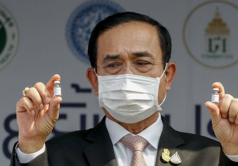 THAILAND. Prime Minister Prayuth Chan-ocha holds samples of Sinovac vaccine during a ceremony to mark the arrival of 200,000 doses of the Sinovac vaccine shipment at Suvarnabhumi airport in Bangkok, Thailand, Wednesday, Feb. 24, 2021. (AP)