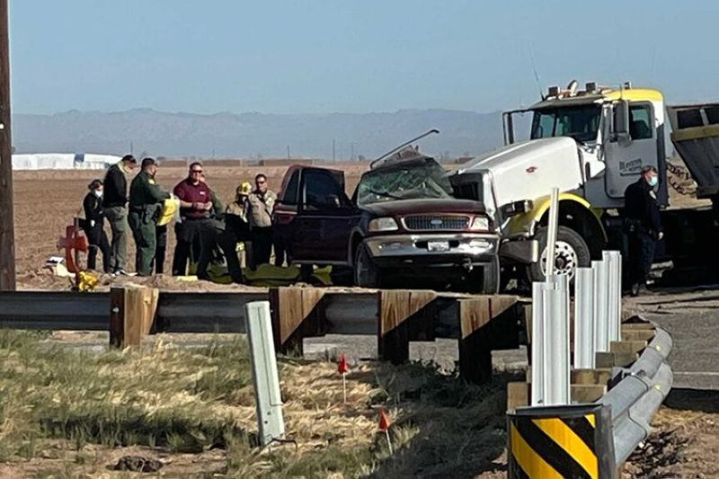 In this image from KYMA law enforcement work at the scene of a deadly crash involving a semitruck and an SUV in Holtville, Calif., on Tuesday, March 2, 2021. (AP photo)