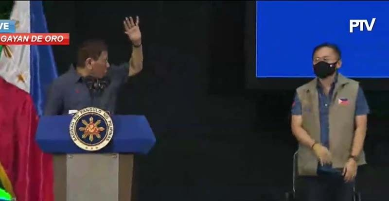 President Duterte instructs Senator Bong Go to waive his hand higher during a gathering in Cagayan de Oro on Friday, March 6, 2021. (Screengrab from PTV)