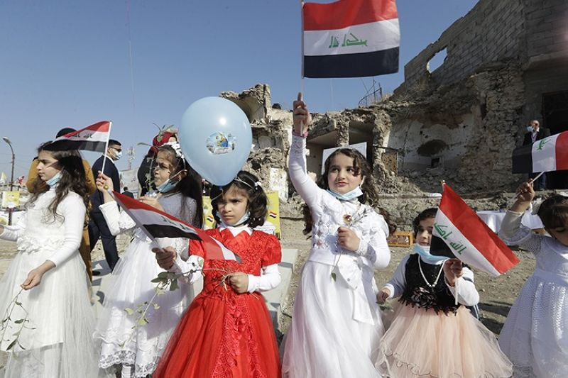 Children in their festive garment wave Iraqi flags to the camera as they arrive to join Pope Francis who will pray for the victims of war at Hosh al-Bieaa Church Square, in Mosul, Iraq, once the de-facto capital of IS, Sunday, March 7, 2021. The long 2014-2017 war to drive IS out left ransacked homes and charred or pulverized buildings around the north of Iraq, all sites Francis visited on Sunday. (AP Photo)