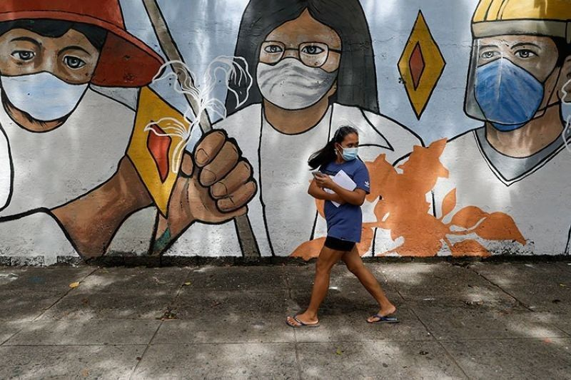 MANILA. In this photo taken in October 2020, a woman wearing protective mask to prevent the spread of the coronavirus walk past a mural showing frontliners in Manila. (AP)